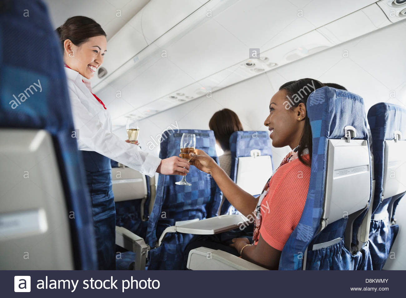 Flight attendant serving champagne to passenger - Stock Image