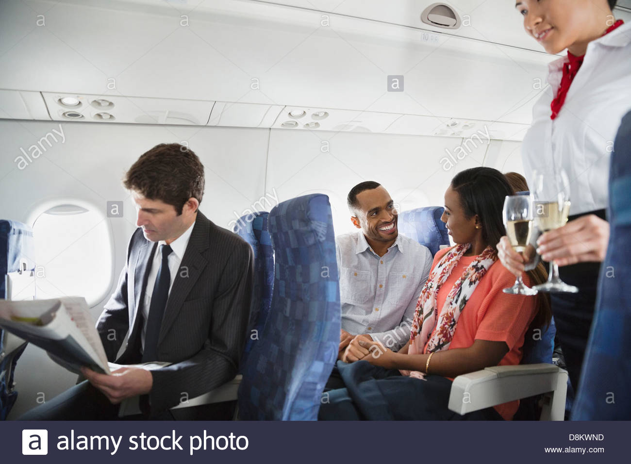 Flight attendant serving drinks to passengers - Stock Image
