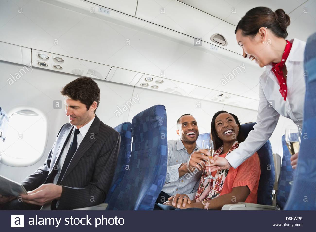 Smiling flight attendant serving drinks to passengers - Stock Image