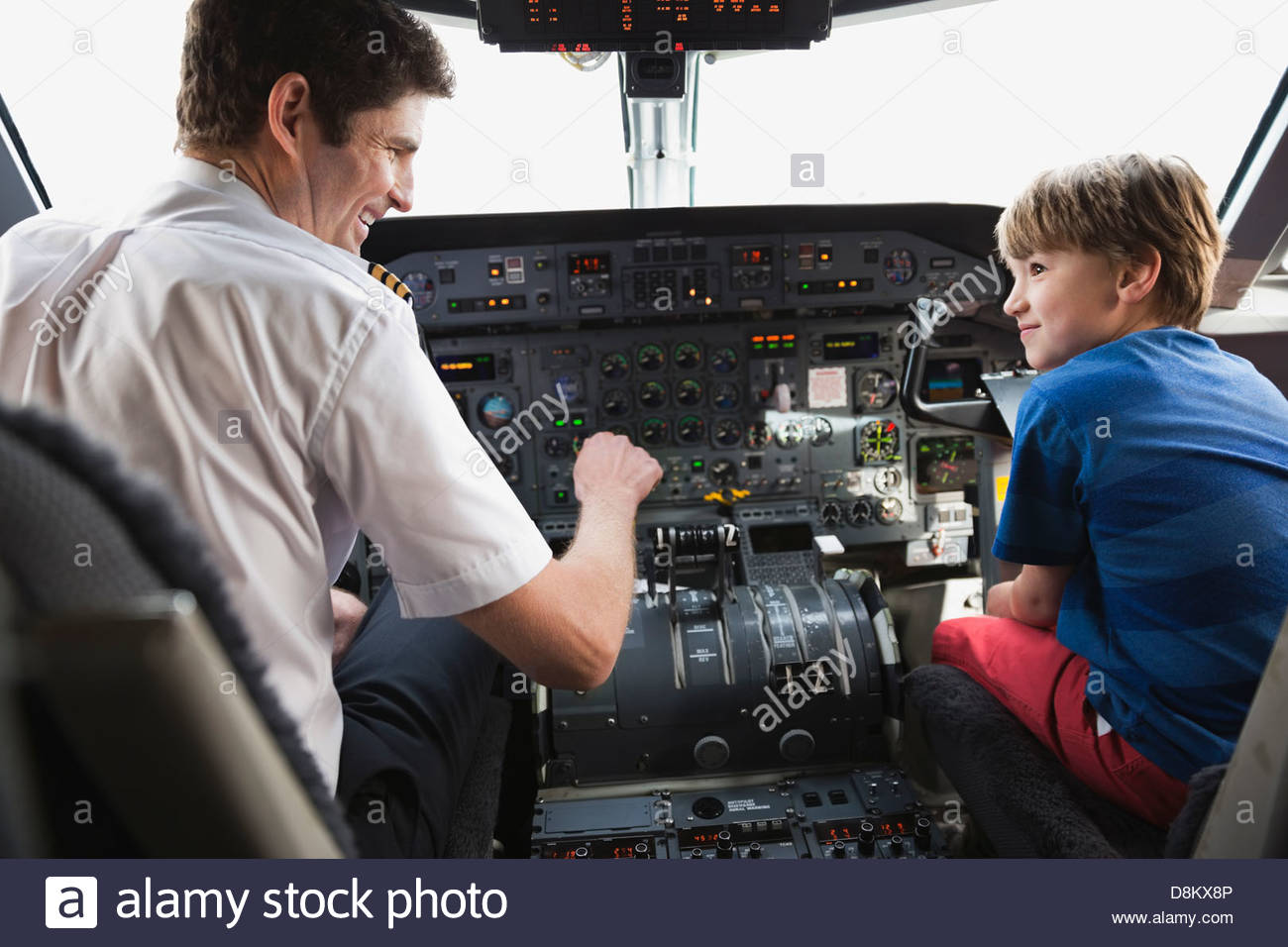 Boy sitting with pilot in airplane cockpit - Stock Image