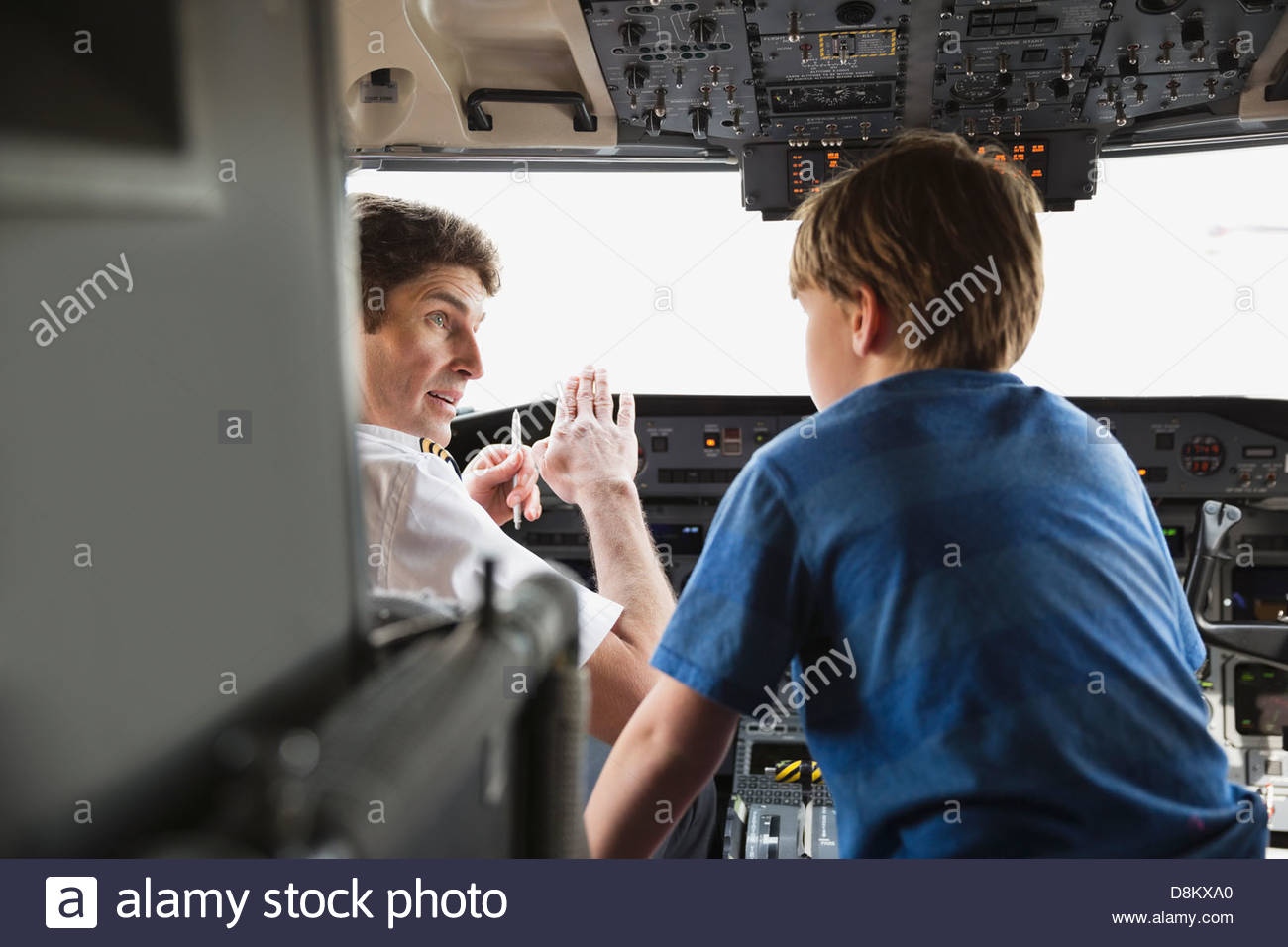 Male pilot explaining control panel to boy in airplane cockpit Stock Photo