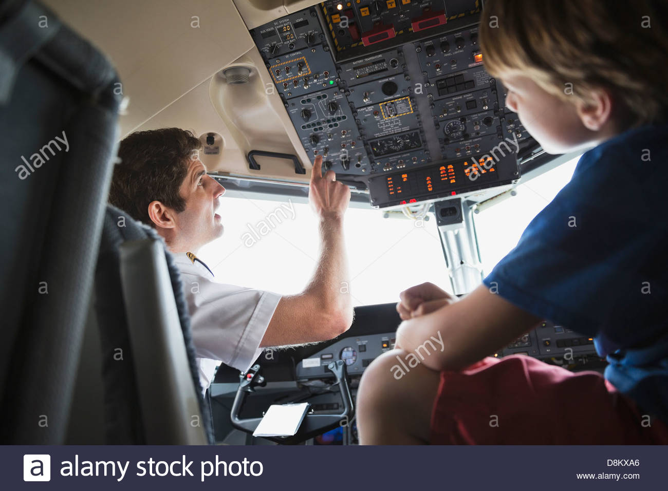 Male pilot explaining control panel to boy in airplane cockpit - Stock Image