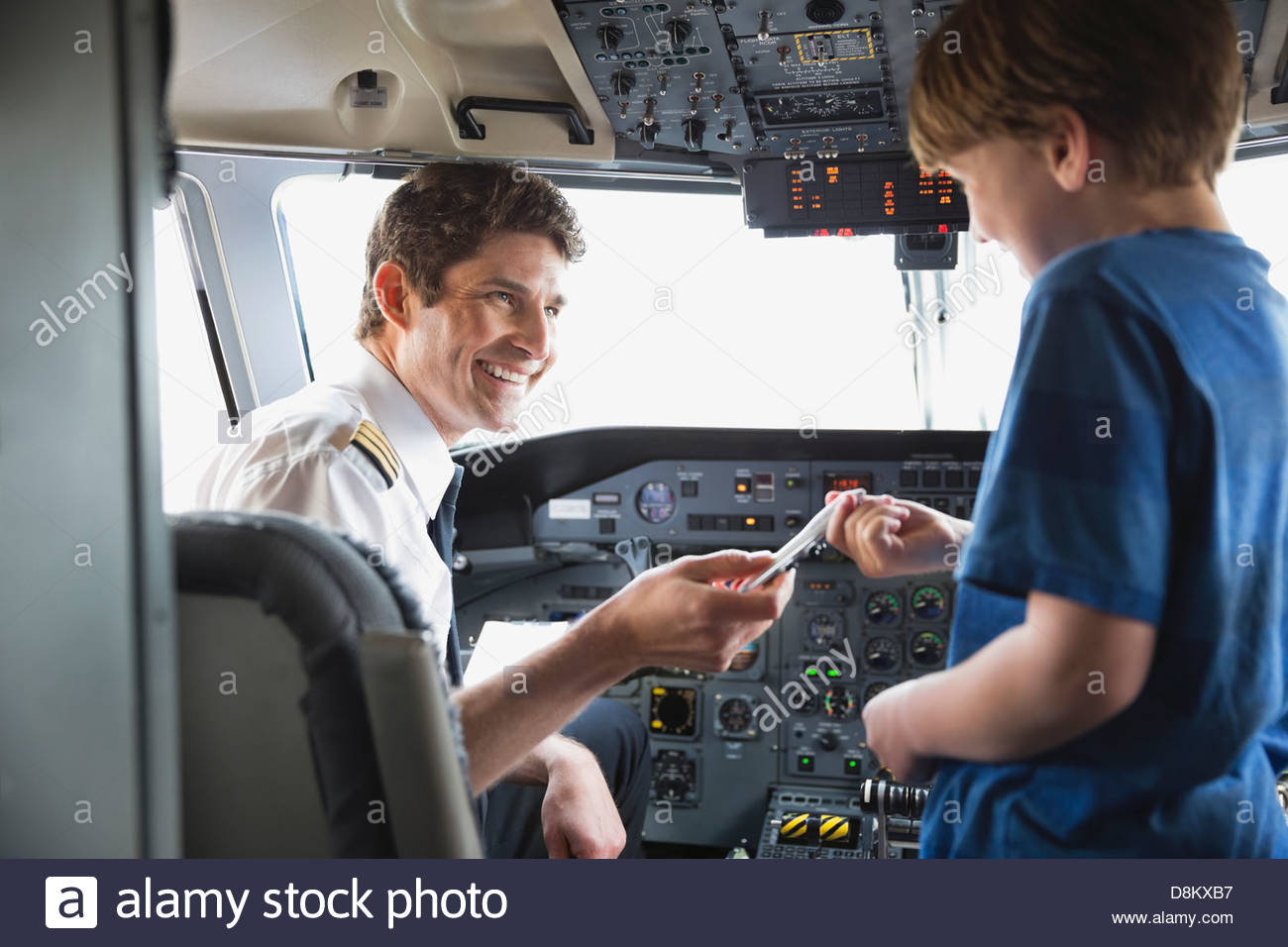 Male pilot giving toy plane to boy in airplane cockpit - Stock Image