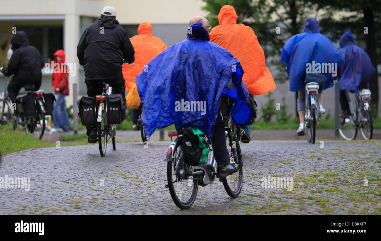 Bicycle riders protect themselves from the rain with rain ponchos in Freyburg, Germany, 30 May 2013. Severe weather - Stock Image