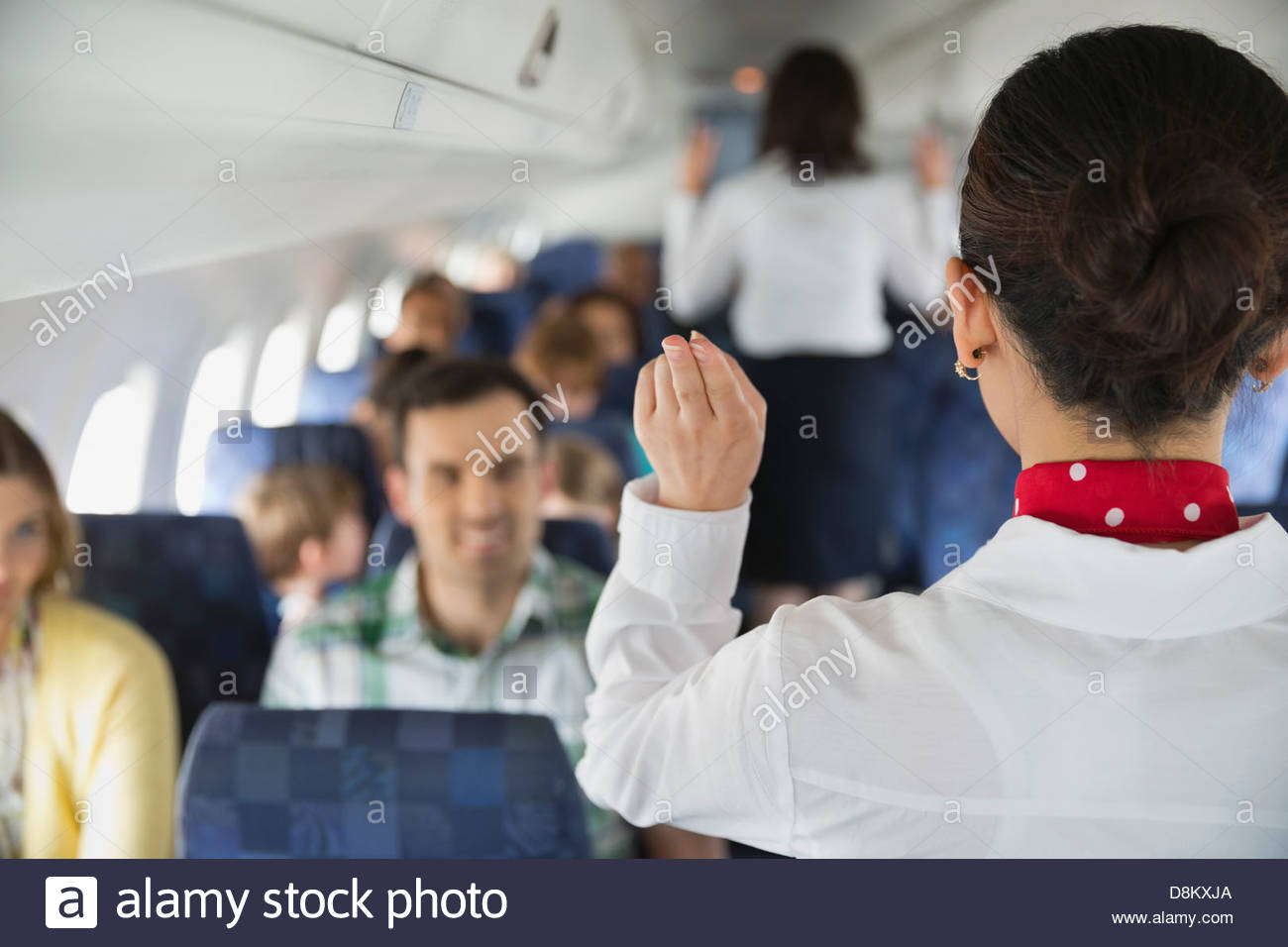 Rear view of flight attendant indicating exits to passengers in airplane - Stock Image