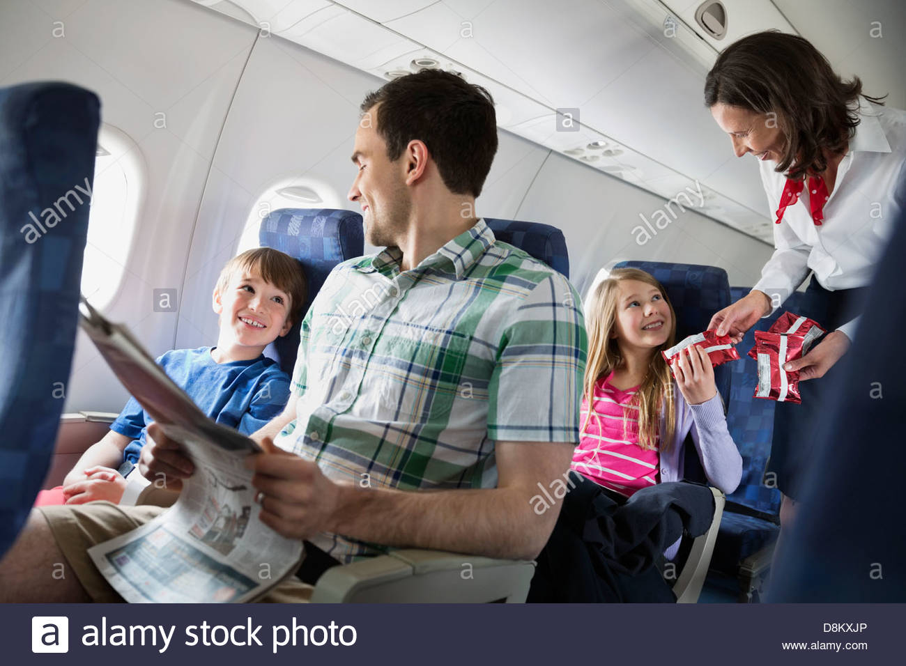 Flight attendant handing out snacks to family in airplane - Stock Image