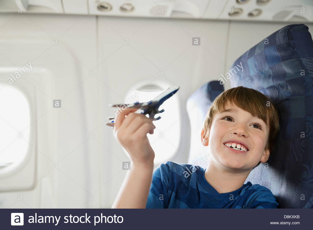 Boy playing with toy plane in airplane - Stock Image