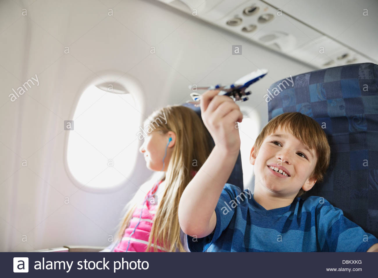 Boy playing with toy plane while sister listens to music in airplane - Stock Image
