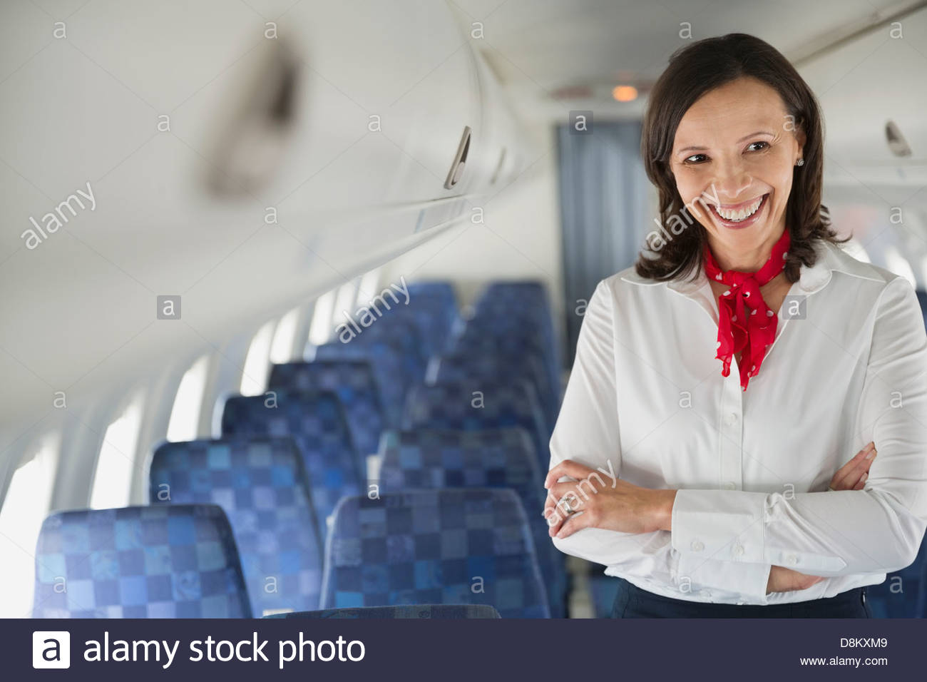 Flight attendant standing with arms crossed in airplane cabin - Stock Image