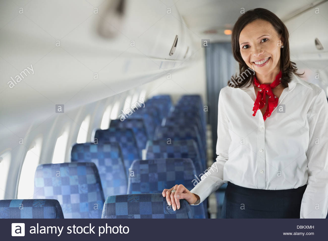 Portrait of flight attendant standing in airplane cabin - Stock Image