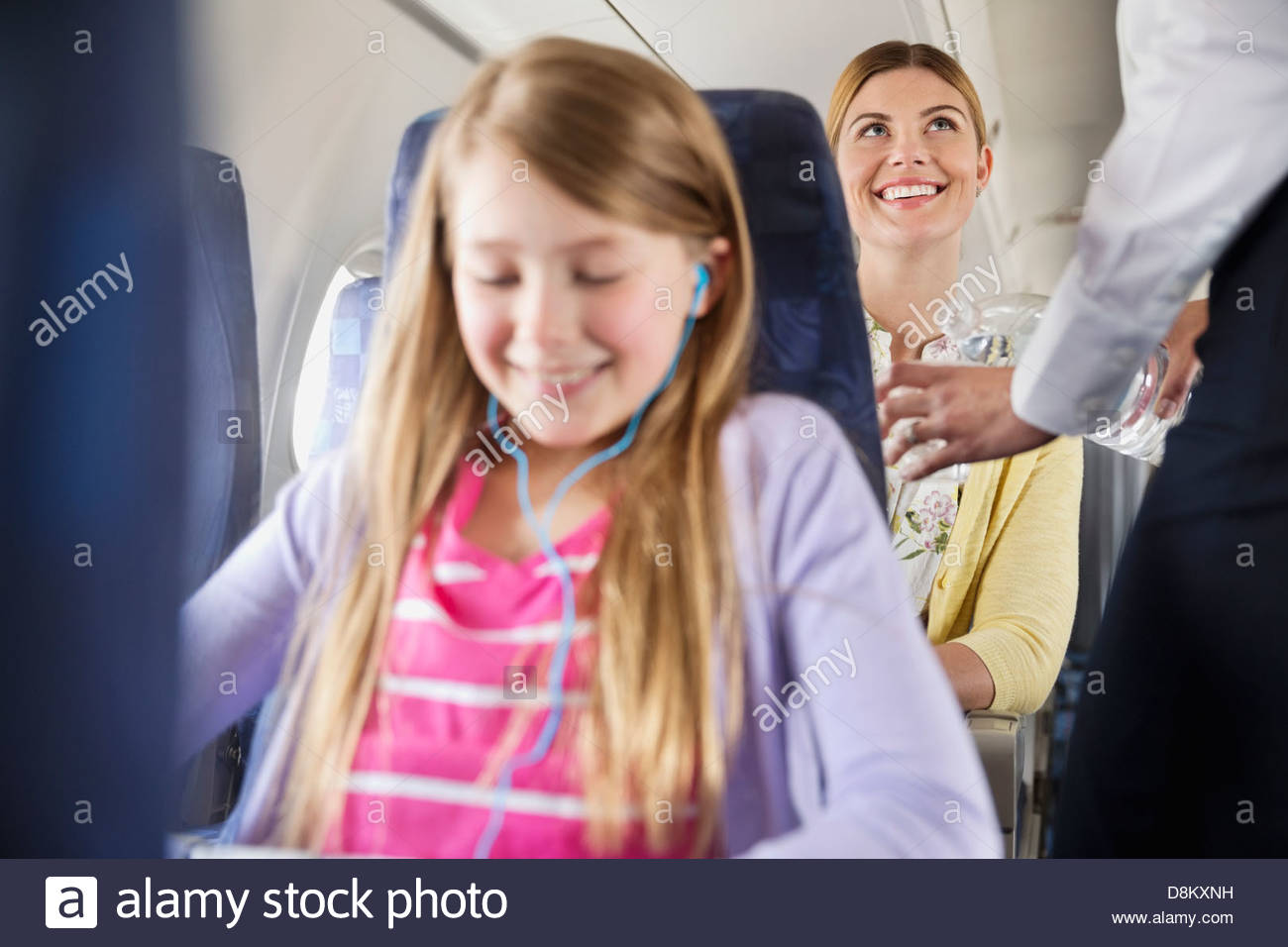 Flight attendant serving water to passenger in airplane - Stock Image