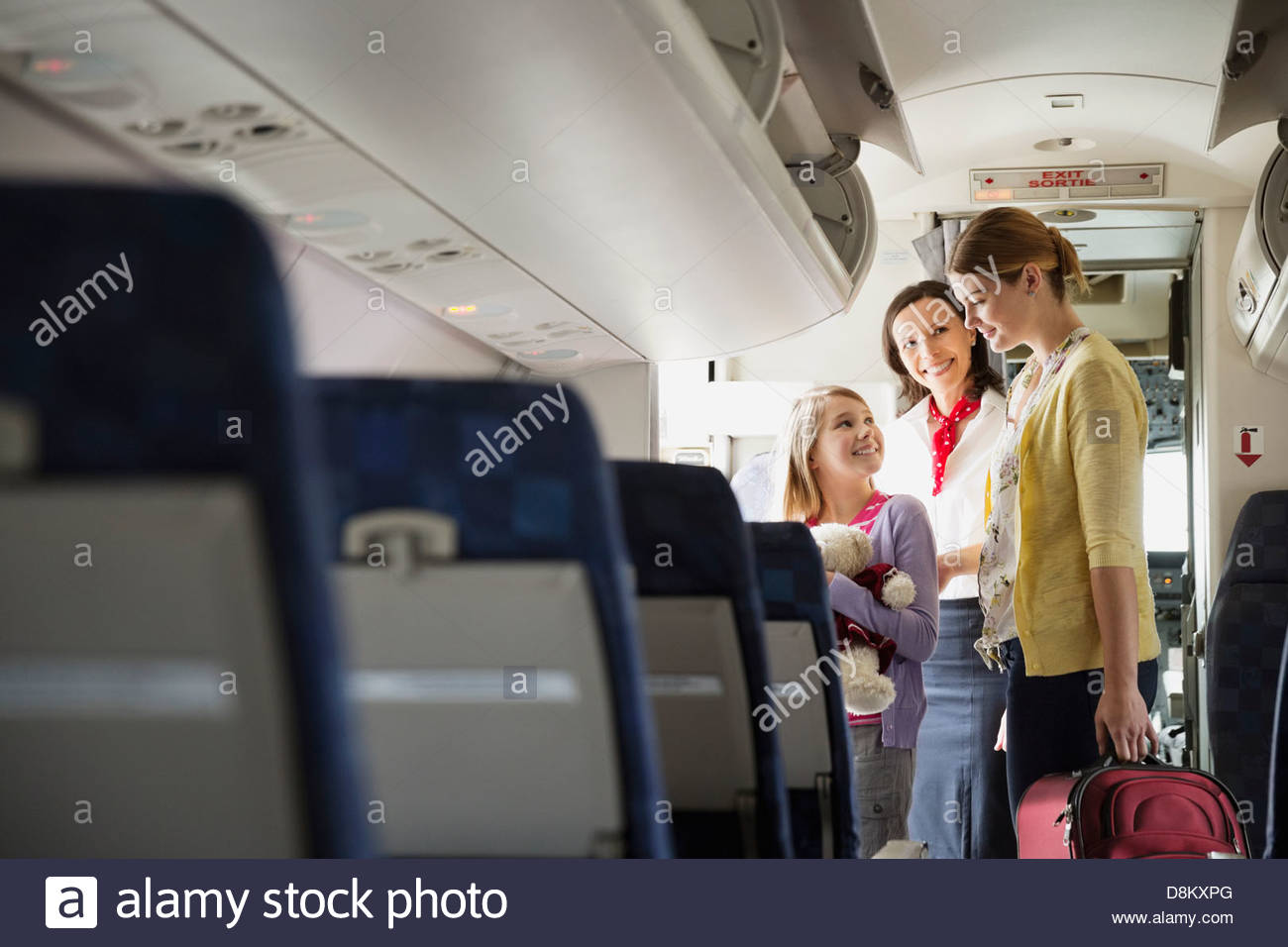 Flight attendant helping woman and daughter disembark airplane - Stock Image