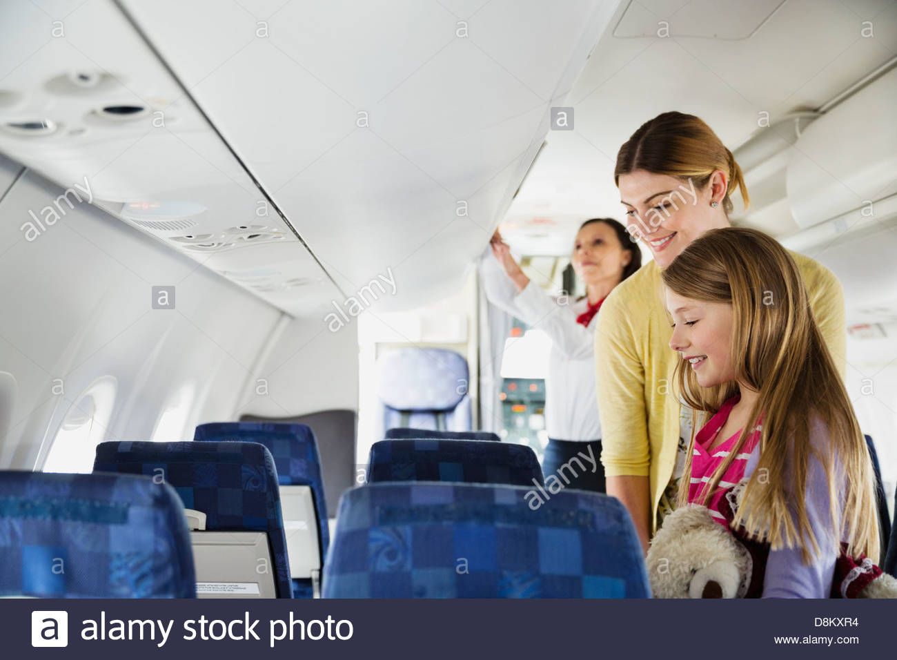 Woman and daughter finding their seats in airplane - Stock Image