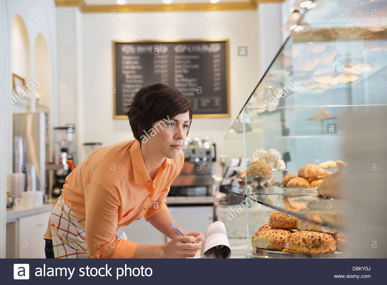 Female small business owner taking inventory in coffee shop - Stock Image
