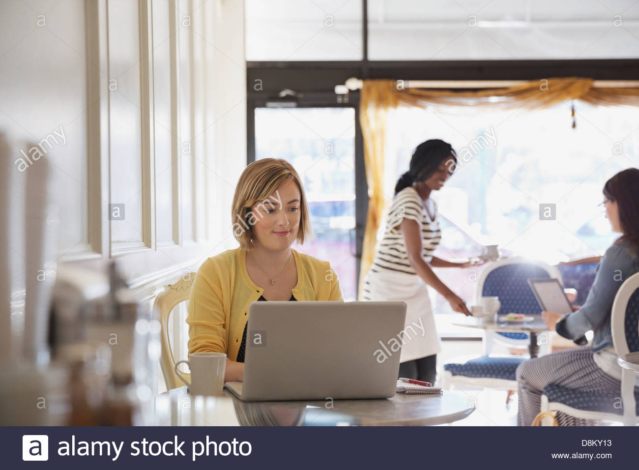 Women using technology at coffee shop - Stock Image