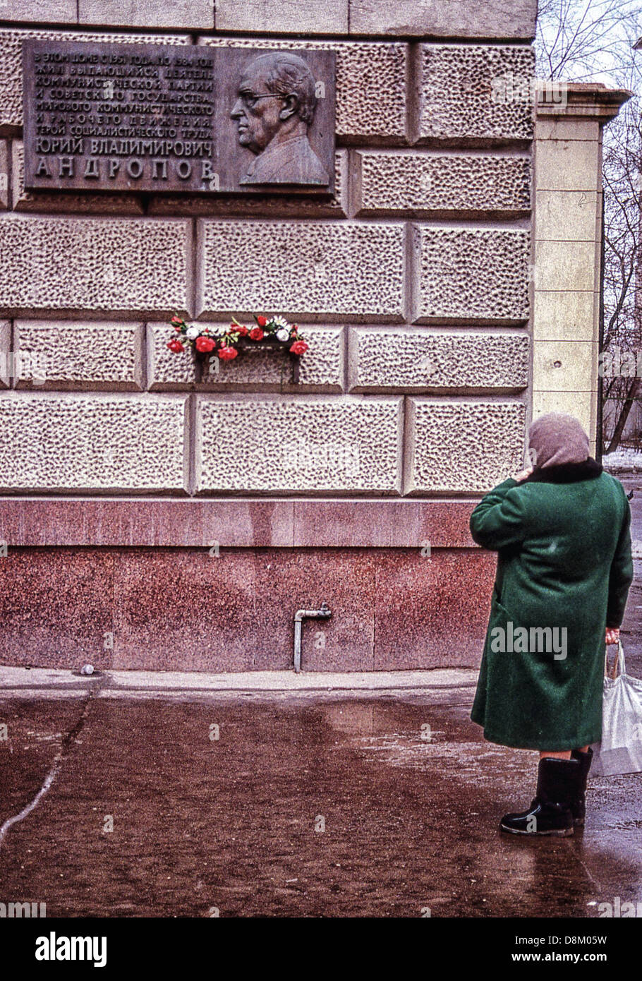 May 31, 2013 - Moscow, RU - A Russian woman views a commemorative plaque, and a shelf with flowers, honoring Soviet - Stock Image