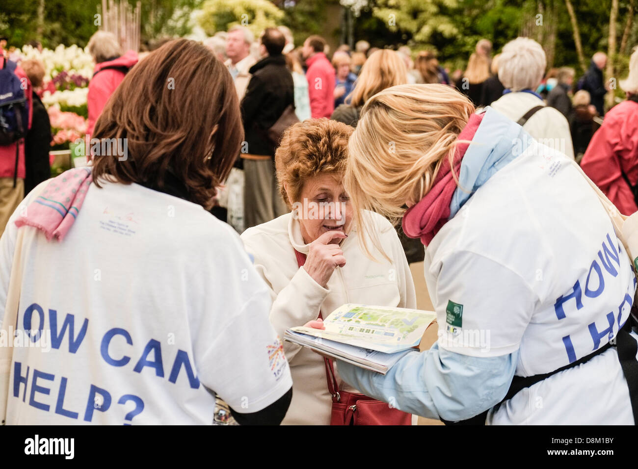A woman asking for assistance at the Chelsea Flower Show. - Stock Image