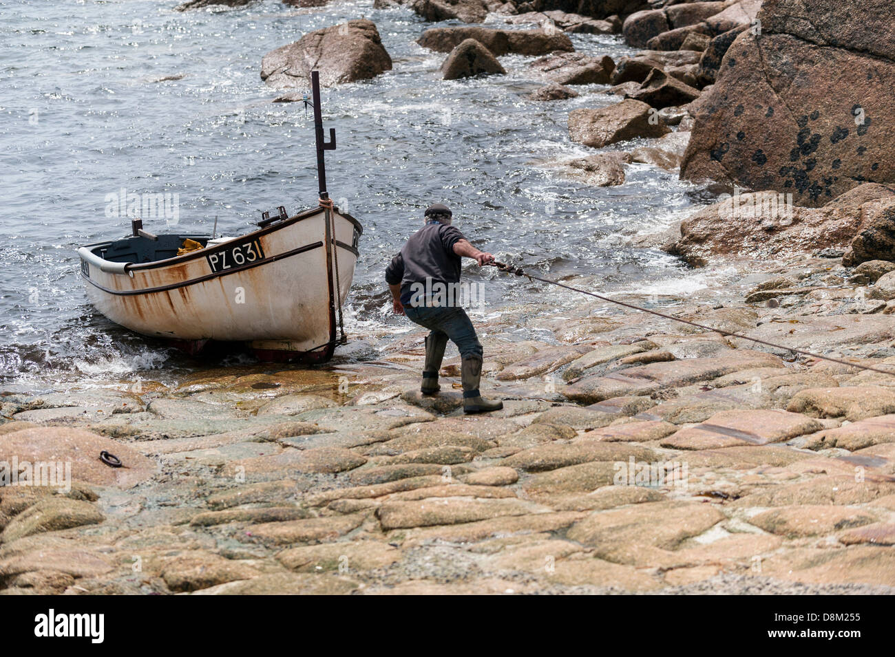 A Cornish fisherman recovering his fishing boat in Penberth Cove. - Stock Image
