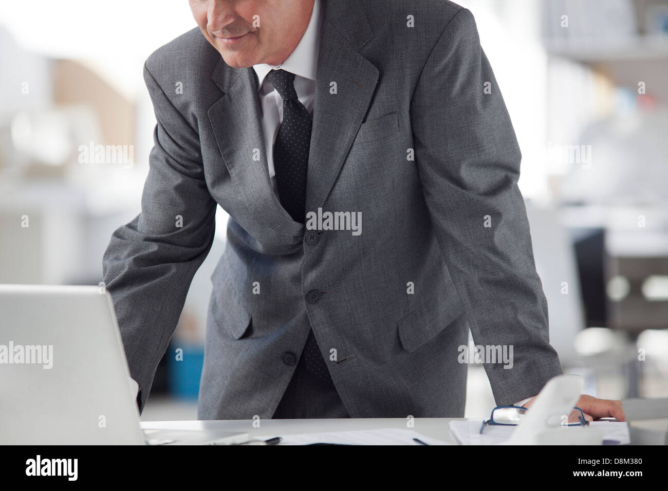 Businessman using laptop computer, cropped - Stock Image