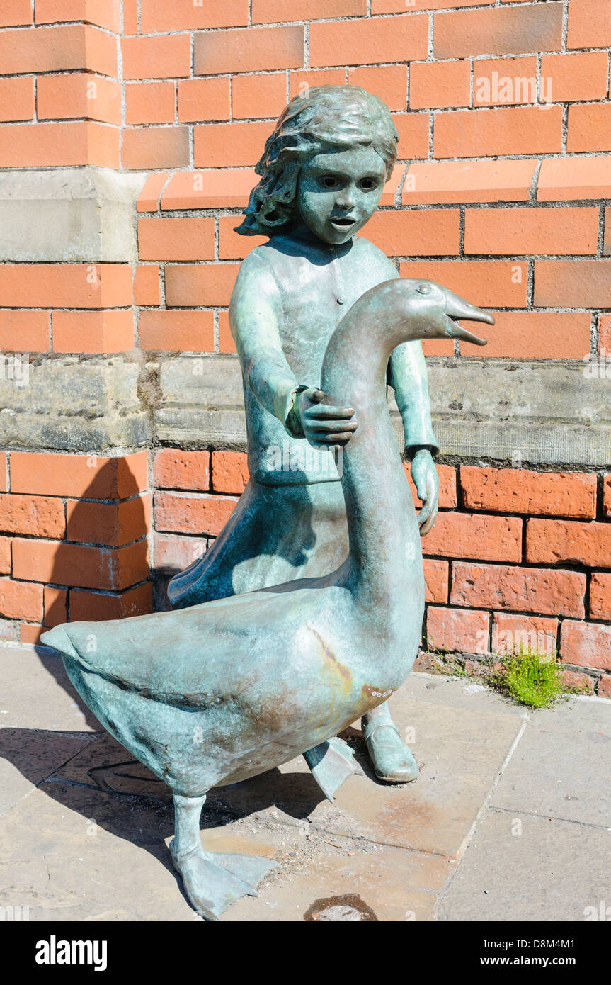 A bronze statue of a girl with 'Alec the Goose' outside St. George's Market, Belfast.  In the 1920s - Stock Image