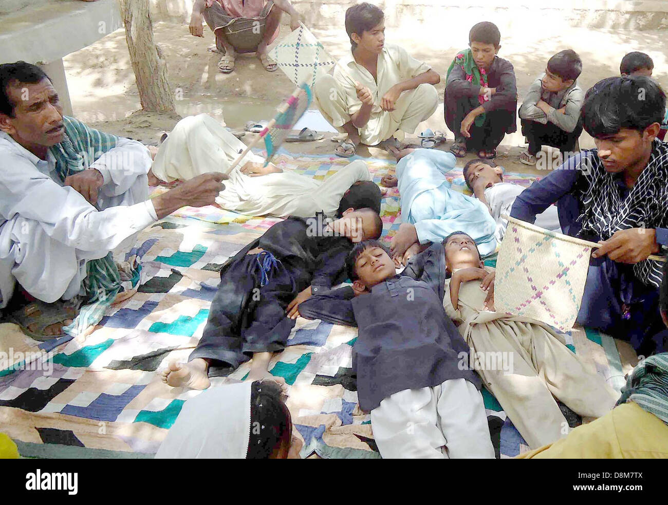 Children, who drink impure toxic water in a school are lying at yard in Sualehpat locality, in Sukkur on Friday, - Stock Image