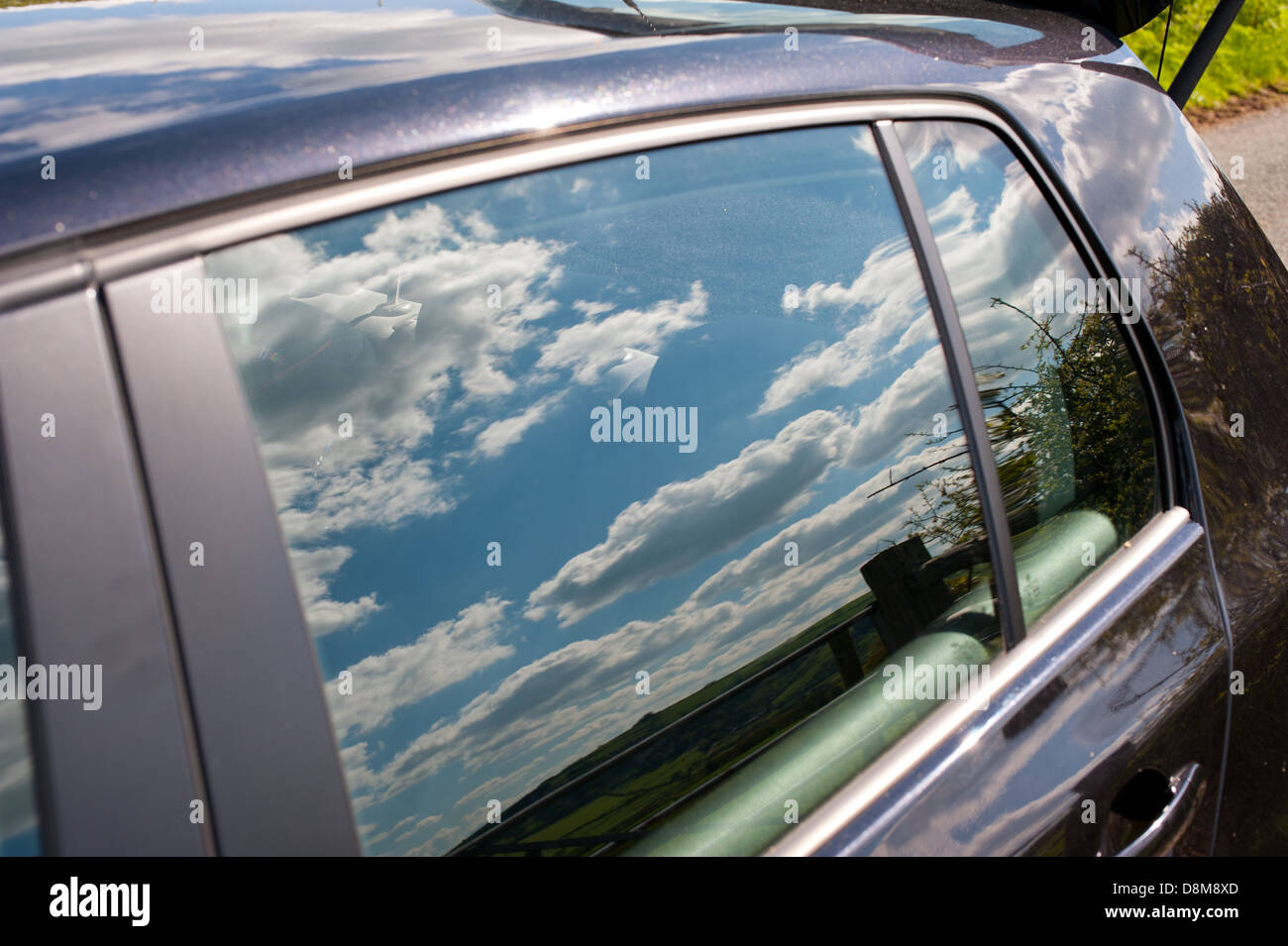 Blue sky and clouds reflected in car window - Stock Image