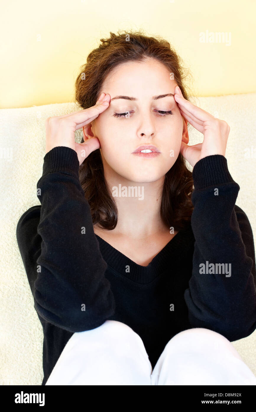 Young woman having headache at home - Stock Image