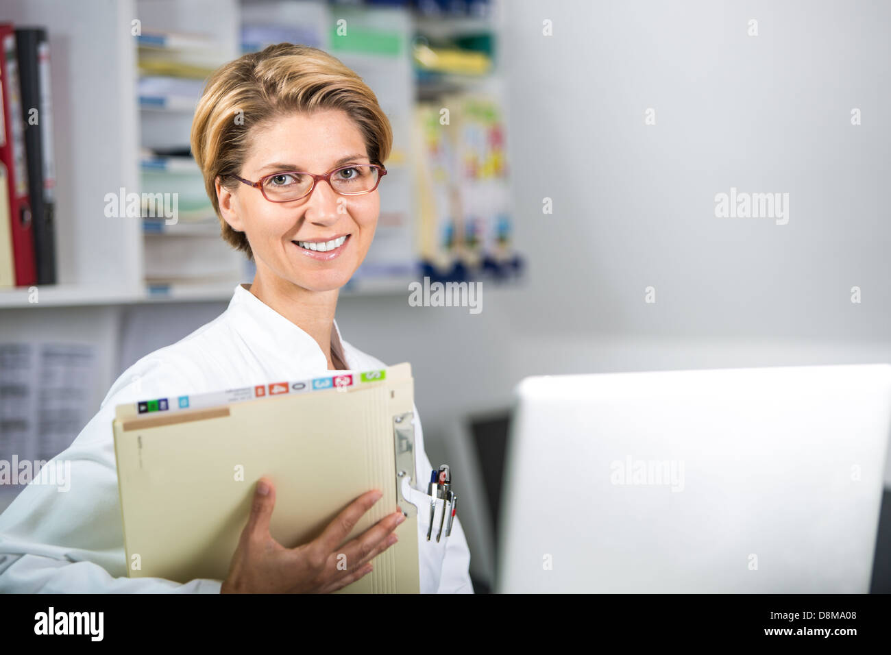 Young doctor with medical records and laptop - Stock Image