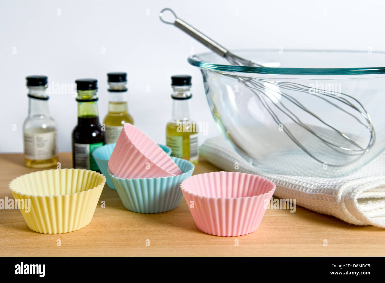 Silicone cup cake wrappers with food colouring and whisk in bowl on wooden chopping board - Stock Image