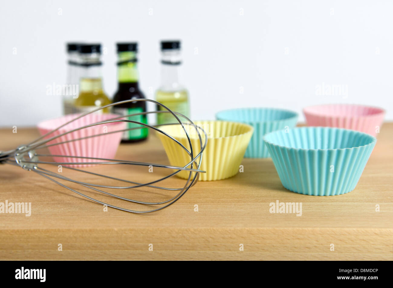 Silicone cup cake wrappers with food colouring and whisk on wooden chopping board - Stock Image