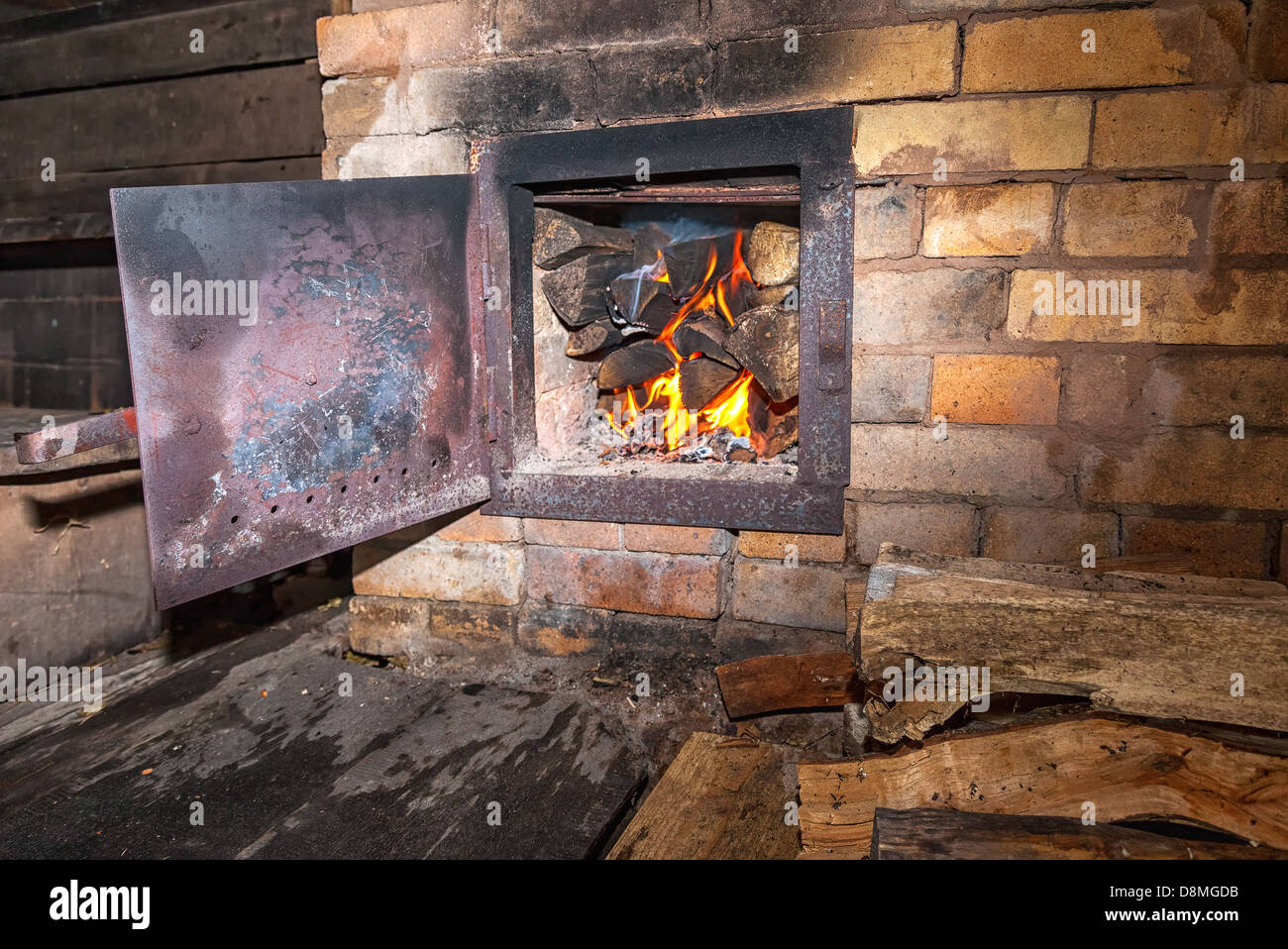 Old stove with open door and burning the wood Stock Photo