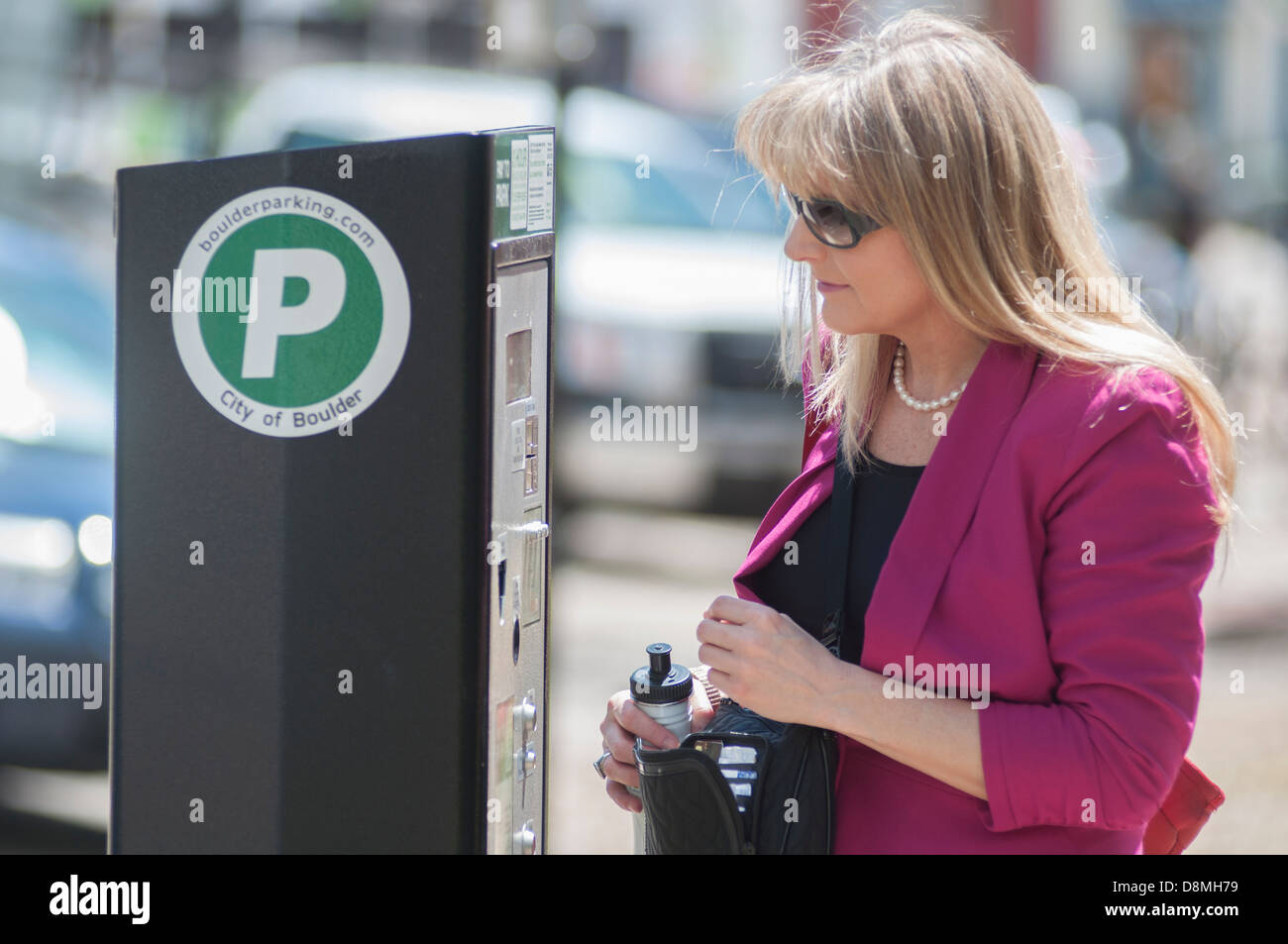 Woman at parking meter. - Stock Image
