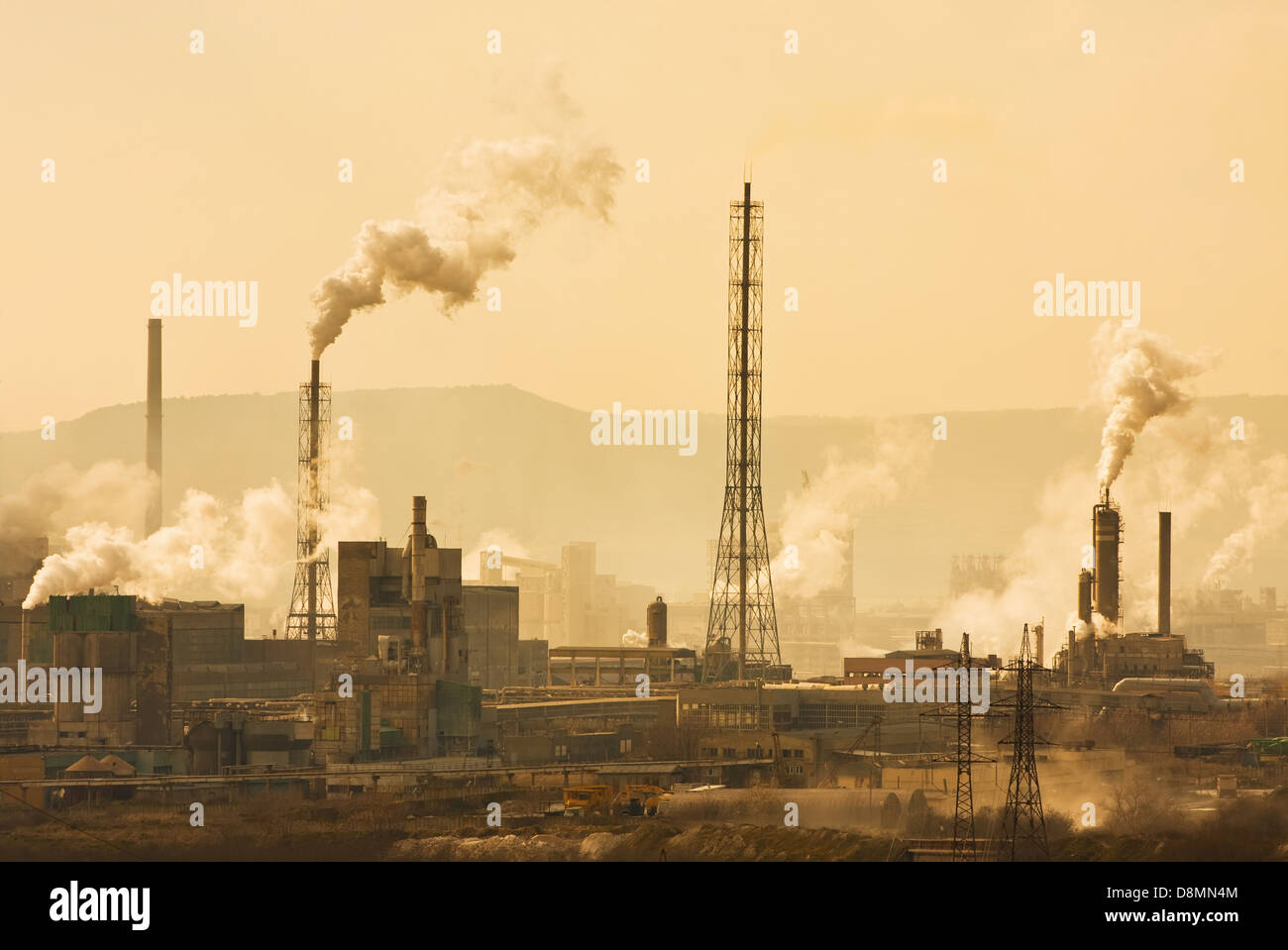 Industrial city with chimneys an refinery - Stock Image