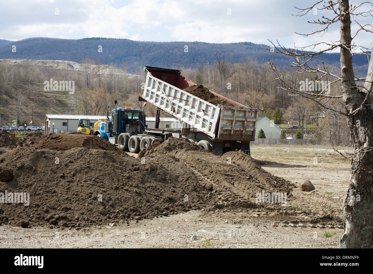 A dump truck begins to unload top soil by a newly constructed building in Adams, Massachusetts. - Stock Image