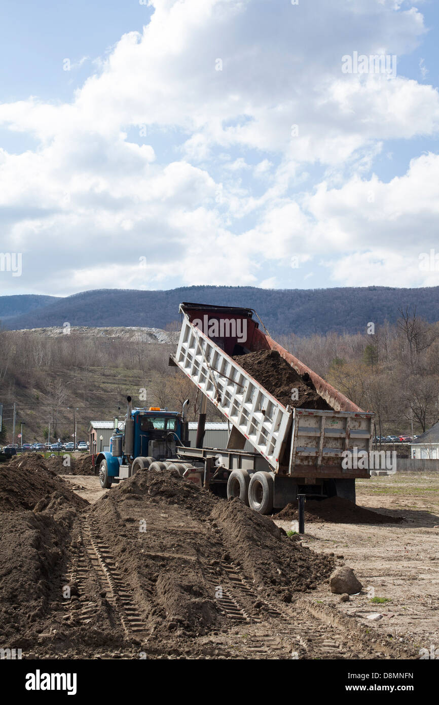 A dump truck unloads top soil by a newly constructed building in Adams, Massachusetts. - Stock Image