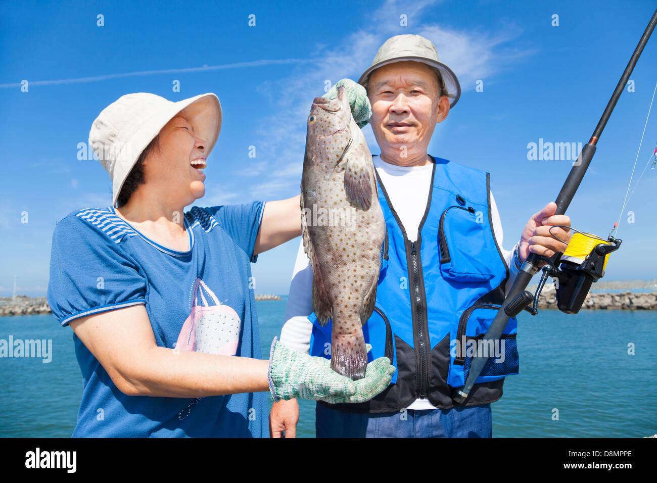 happy asian senior couple fishing and showing big grouper - Stock Image