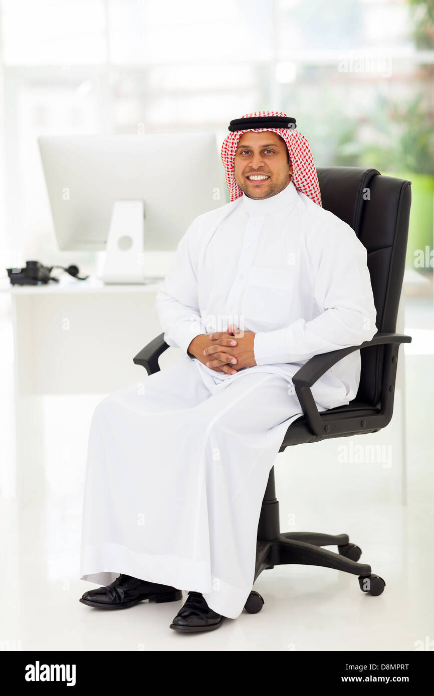 smiling middle eastern businessman sitting in modern office - Stock Image