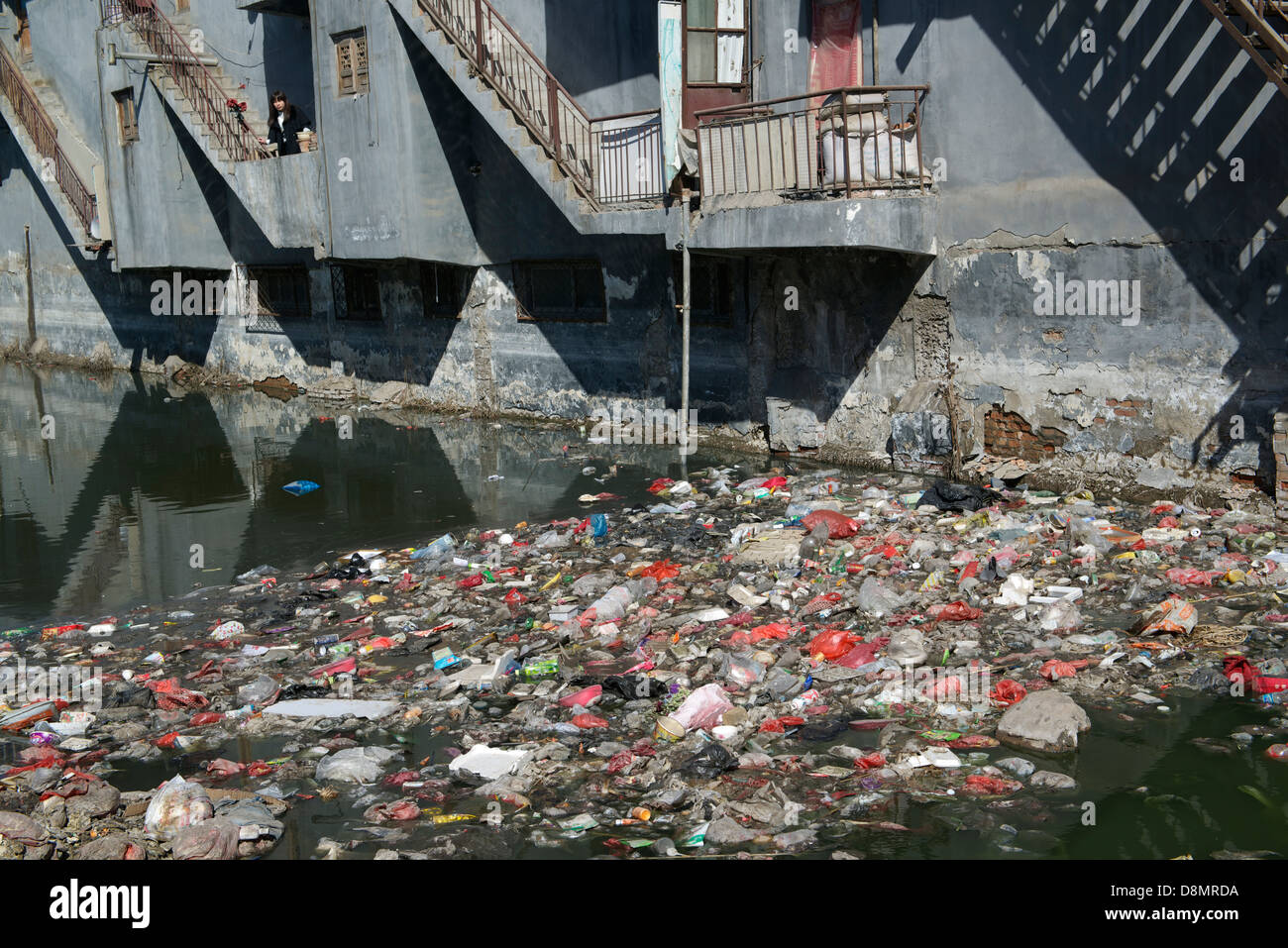 Liu Lu,  a native resident, stands at a balcony over a badly polluted river by garbage and industrial wastewater - Stock Image