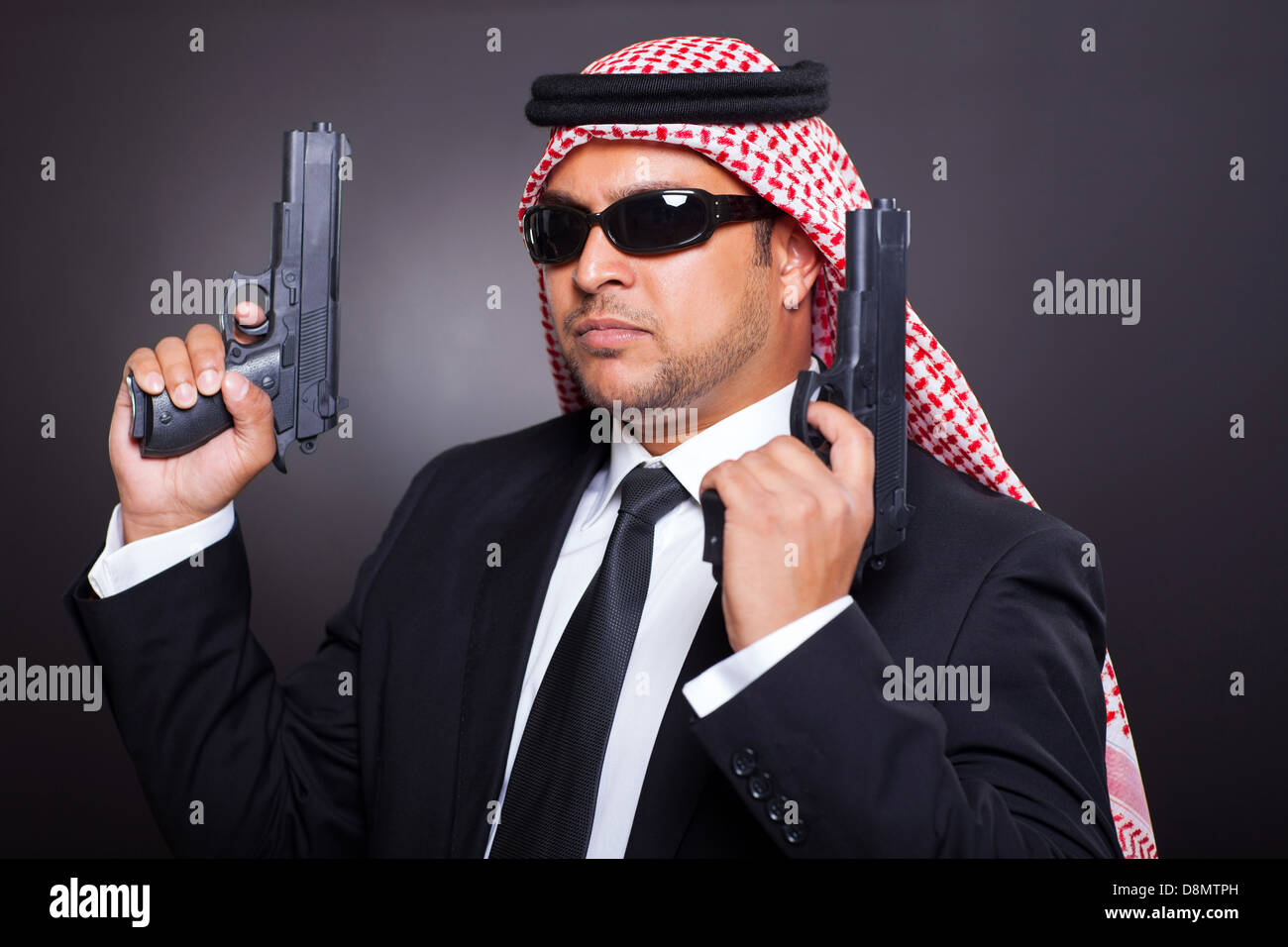 Young Middle Eastern Hitman Posing With Guns Over Black Background Stock Photo Alamy