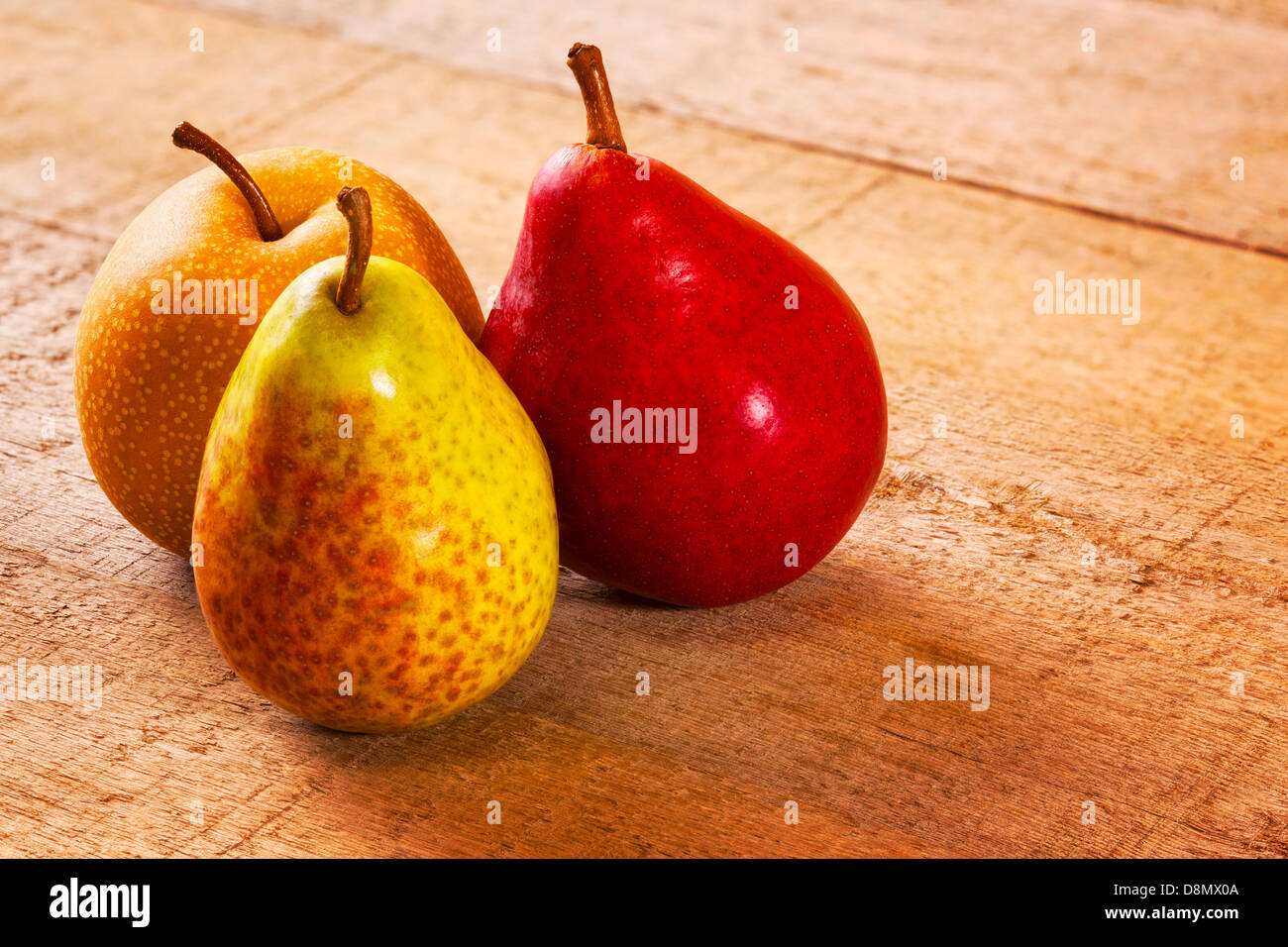 Pears on a Rustic Wood Surface - three different pears on a rustic wooden plank surface... - Stock Image