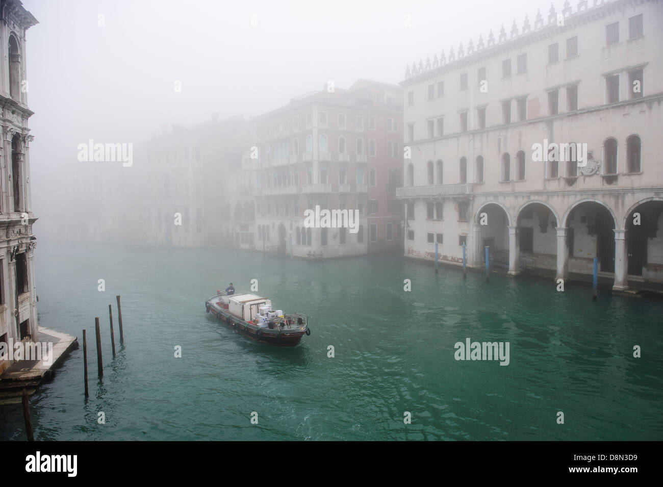 A delivery boat sails in the Grand Canal of Venice covered with thick fog, Italy. - Stock Image