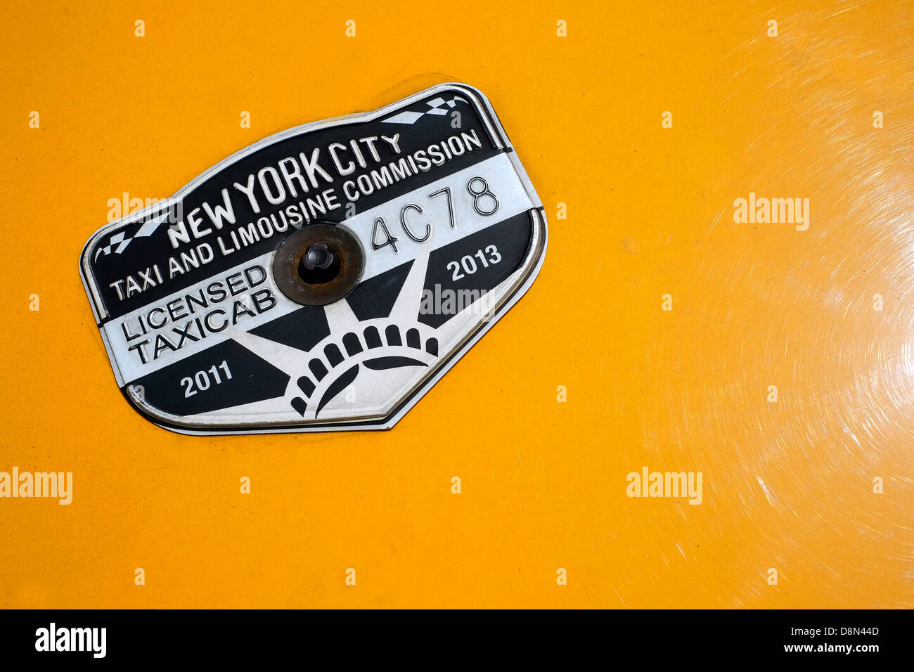 New York City Taxi & Limousine Commission badge on the hood of an NYC taxi. - Stock Image