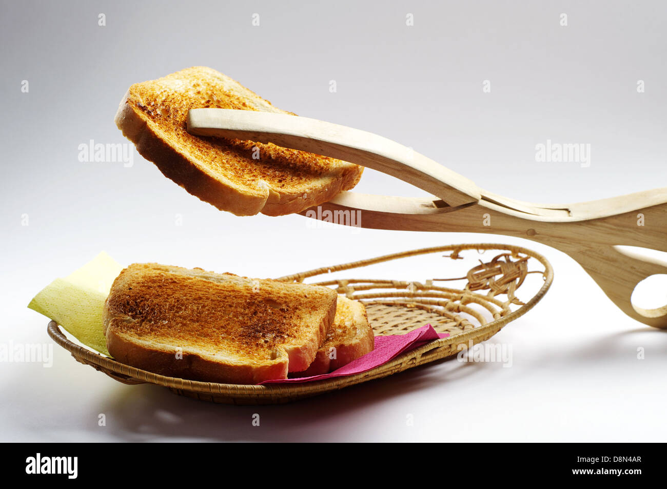 Toast and wooden tongs for bread - Stock Image