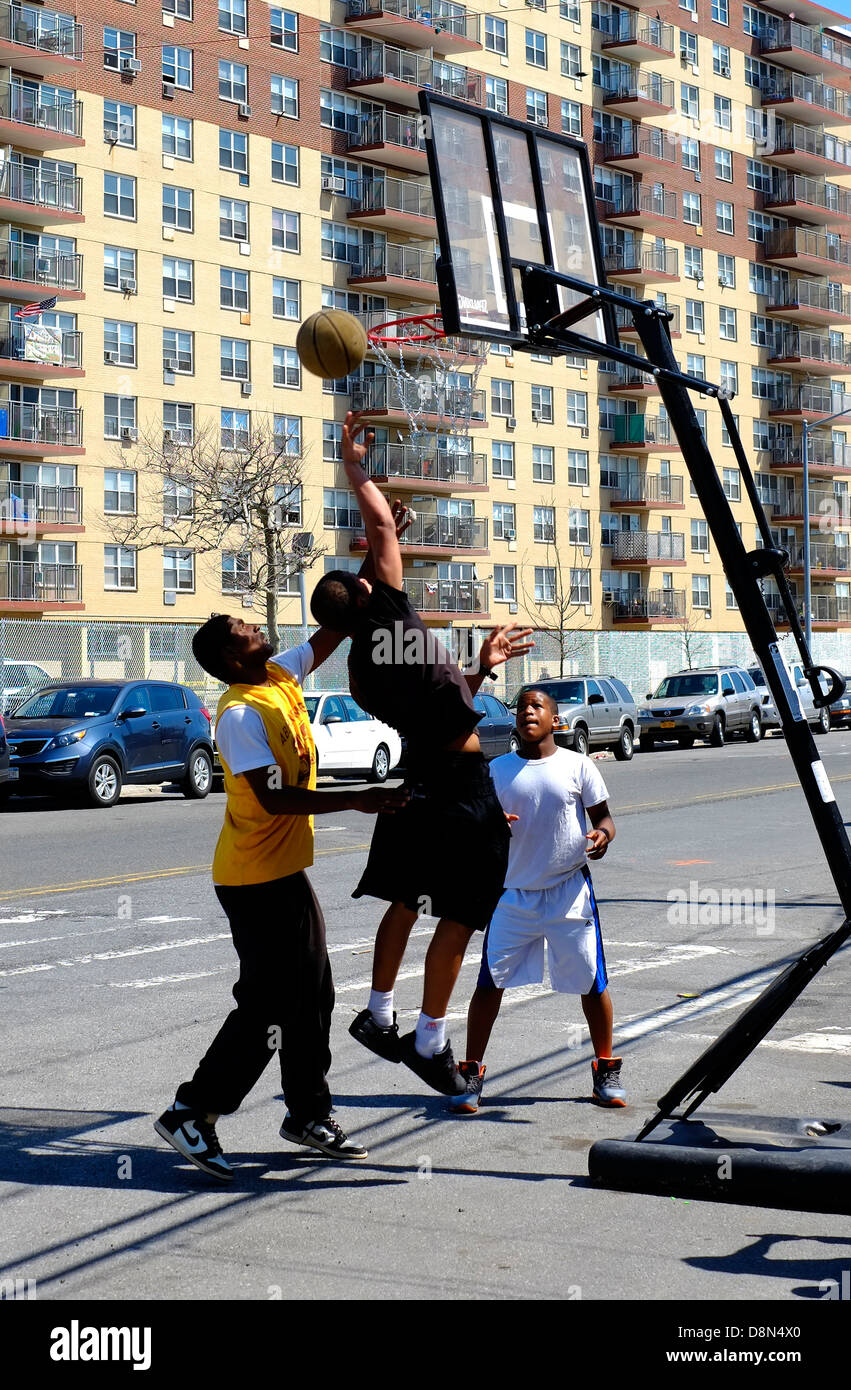 Three men play basketball on the street in Long Beach, New York. - Stock Image