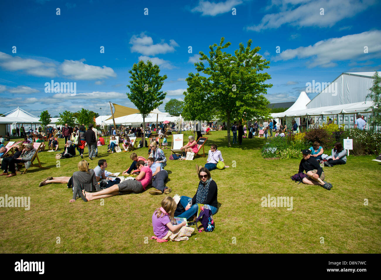 Visitors enjoying the warm summer weather relaxing on the lawn at Hay Festival 2013 Hay on Wye Powys Wales UK - Stock Image