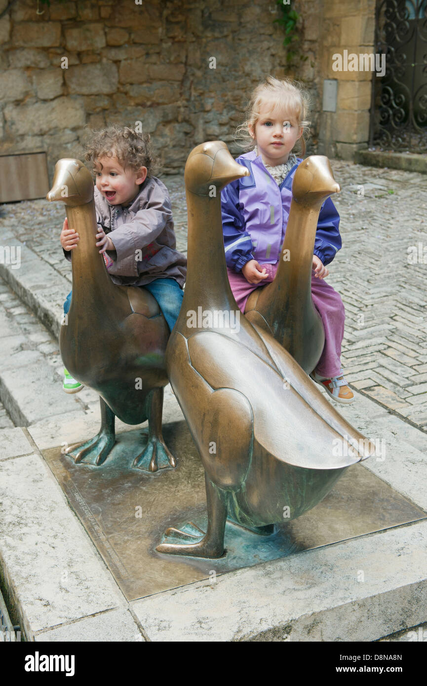 Children play on Goose statue in Place aux Oies (Goose Square) Sarlat-la-Canéda, Dordogne FRANCE, well-preserved - Stock Image