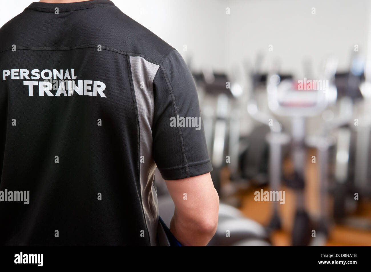 Personal Trainer, with his back facing the camera, looking at a gym - Stock Image