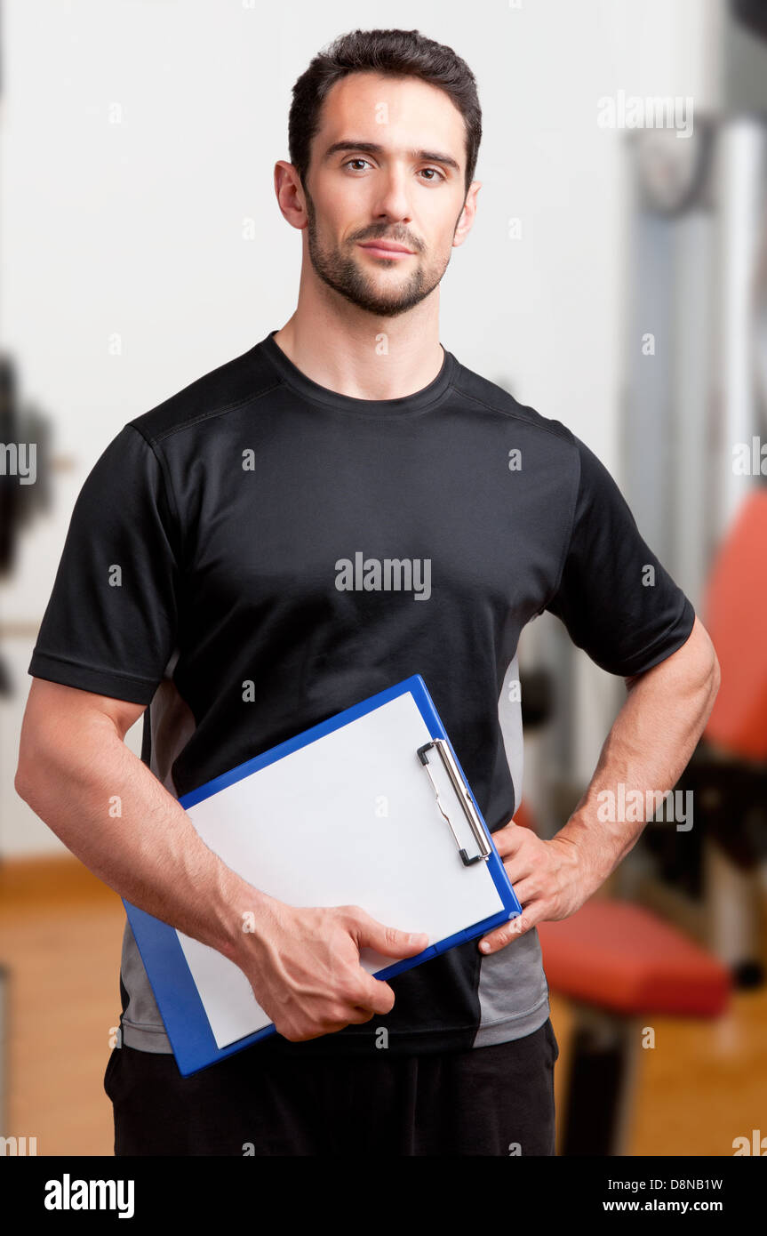 Personal Trainer, with a pad in his hand, in a gym - Stock Image