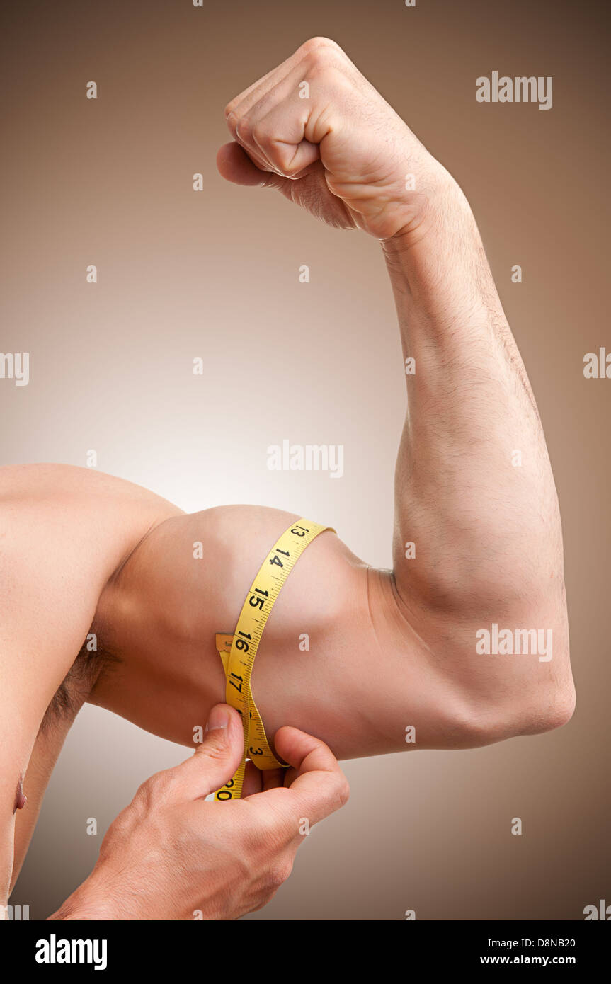 Fit man measures his bicep with a yellow tape - Stock Image
