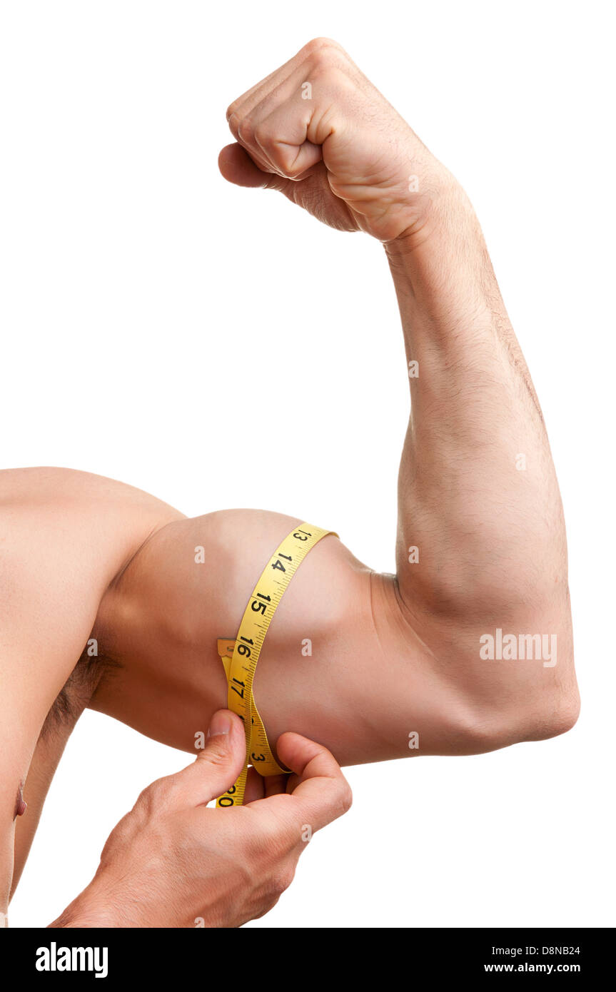 Fit man measures his bicep with a yellow tape, isolated in white - Stock Image